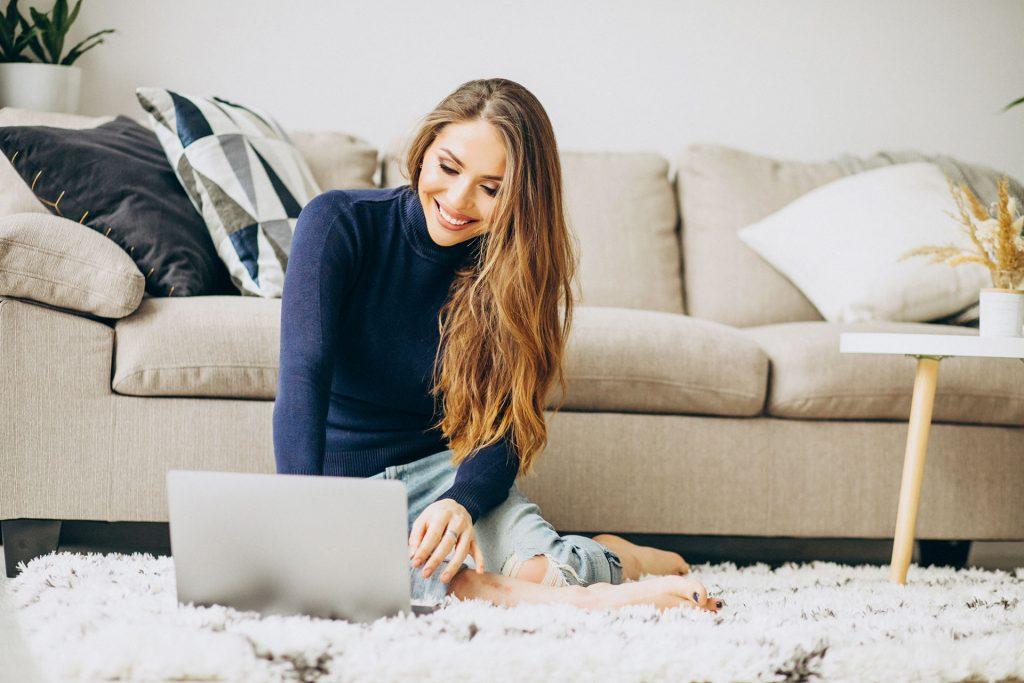 Frau sitzt auf Boden und sieht auf einen Laptop
